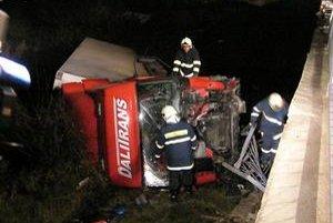 Hasiči v akcii. Vodič kamióna vyviazol len s ľahkými zraneniami.