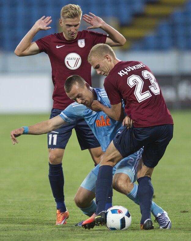 Boris Sekulič bojuje o loptu s dvomi hráčmi Jelgavy.