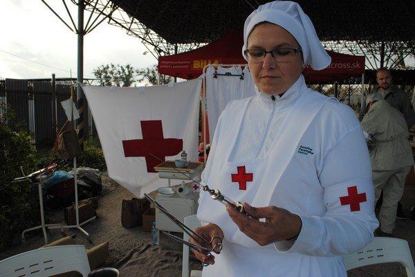 Tatiana Zubová v dobovom oblečení zdravotných sestier ukazuje nástroje, aké sa v minulosti používali.