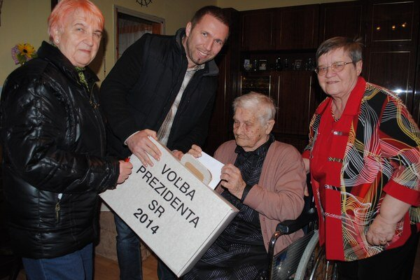 S prenosnou urnou za ňou prišli členovia okrskovej volebnej komisie Michal Parnica a Irena Babinová. Na snímke vpravo dcéra Marta Nováková, ktorá sa o mamičku vzorne stará už roky.