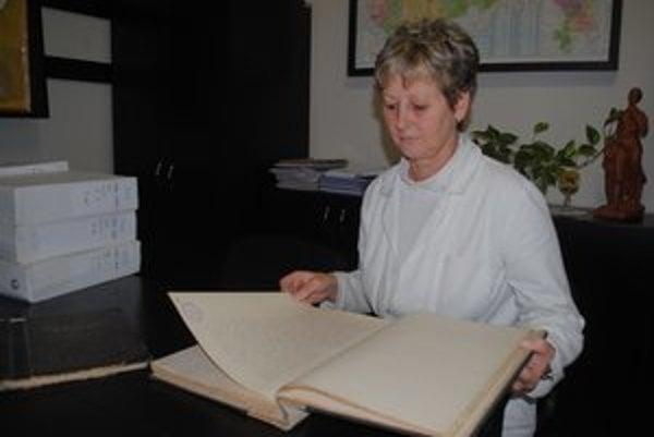 Mária Novosádová. Riaditeľka humenskej pobočky Štátneho archívu si prezerá kroniku Humenného z medzivojnového obdobia.
