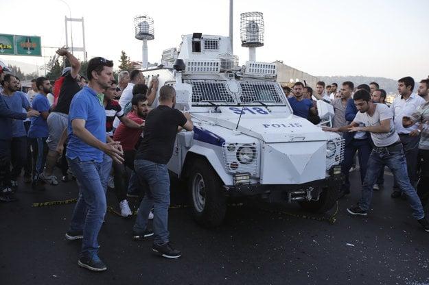 Ľudia útočia na policajné auto, ktoré preváža zadržaných vojakov.