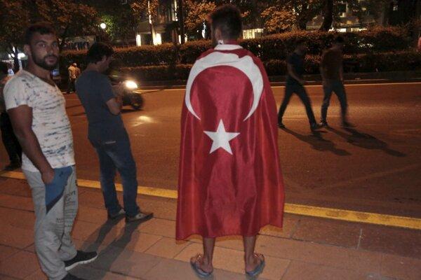 Muž v tureckou vlajkou v uliciach Ankary.