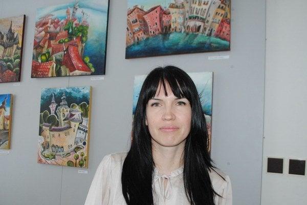 Lucia Chocholáčková. Autorka sa vo svojej tvorbe inšpiruje mestami, ulicami, budovami a hradbami.
