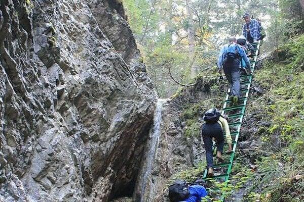 Turisti v Slovenskom raji. Majú za sebou aj dosť náročný výstup po zelenej značke zabezpečený stúpadlami, rebríkmi či reťazami.