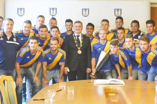 Spoločná fotografia s primátorom. Michalovskí futbalisti prišli ukázať Viliamovi Zahorčákovi aj víťazný pohár.
