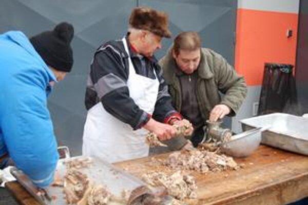 Zabíjačkové pochúťky. Chlapi pripravujú mäso na jaternice.
