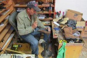 Majster obuvník. Opravuje opätky na topánkach.