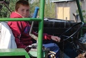 Na traktore. Lacko povolil ručnú brzdu, vyhodil rýchlosť a točil volantom, aby mohli traktor vytiahnuť z plameňov.
