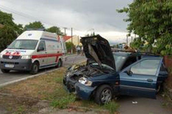 """Auto na chodníku. Ford odhodilo po čelnej zrážke na chodník. Jeho zadná časť sa """"zapichla"""" do plota."""