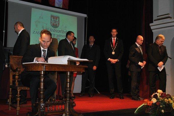 Primátor a jeho zástupca. Zástupca J. Cvoliga pri podpisovaní sa po zložení poslaneckého sľubu. Vpravo vzadu primátor M. Majerský.