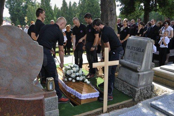 Na snímke horskí záchranári ukladajú rakvu do hrobu počas štátneho pohrebu náčelníka Horskej záchrannej služby v Slovenskom raji Dušana Leskovjanského.