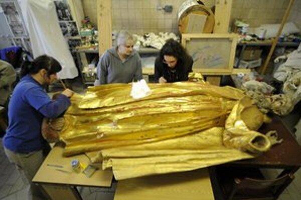 Pracovníčky reštaurátorského ateliéru čistia drevenú sochu Antona Pustovníka z kostola v Červenom Kláštore.