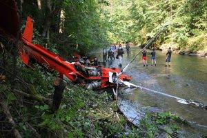 Polícia, vyšetrovatelia a záchranári skúmajú spadnutý vrak vrtuľníka.