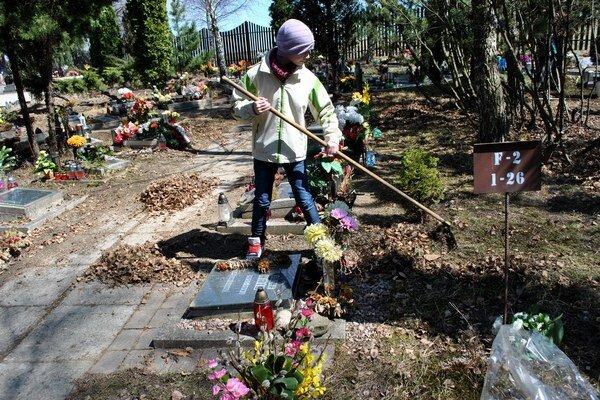 Práca im išla od ruky. Deti usilovne čistili okolie hrobov.