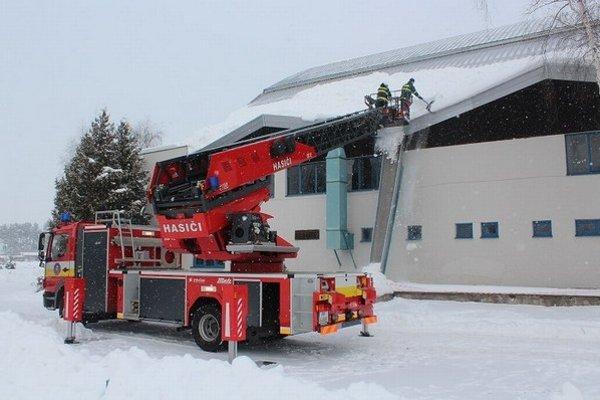 Hasiči. Pomáhali odstraňovať sneh zo strechy.