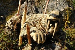 Na snímke drevená plastika šabľozubého tigra chyteného do pasce.