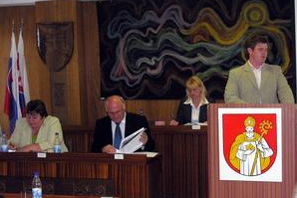 Mestské zastupiteľstvo. Primátor Valent Jaržembovský (sediaci), poslancov presviedča jeho syn (vpravo).