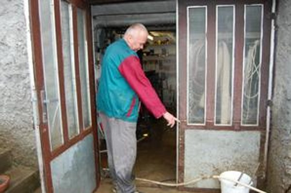 Jozef Tomáško. Ukazuje, kam až sa vyšplhala hladina vody. Za 54 rokov si čosi také nepamätá.