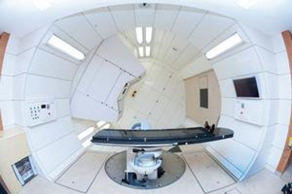 """Stôl v otočnom """"gantry"""". Gantry je otočný portál, ktorý umožňuje nasmerovať iónový lúč presne na tumor."""