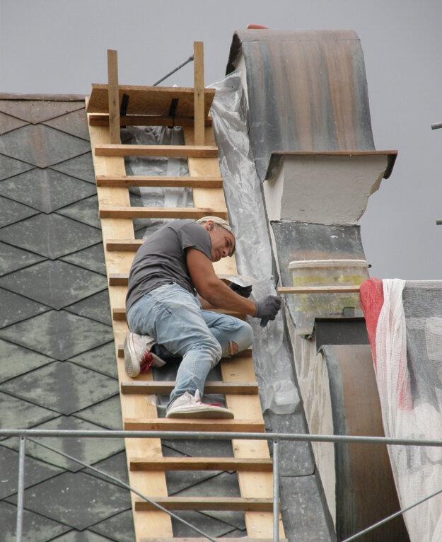 Reštaurátor na streche kostola.