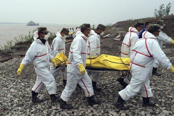 Čínski záchranári nesú telo obete z potopenej lode v rieke Jang-c'-ťiang.