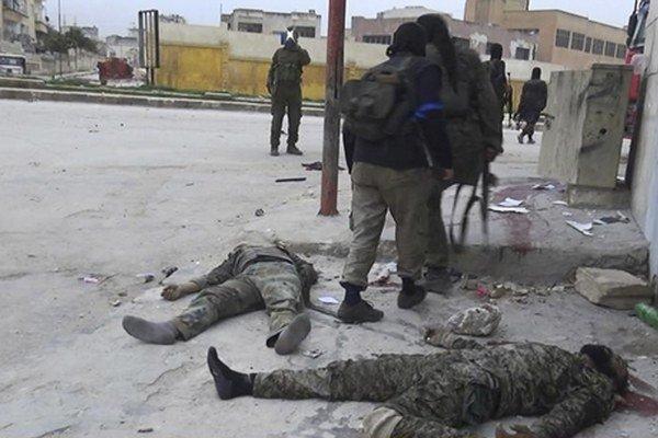 Bojovníci Frontu an-Nusra chodia okolo tiel padlých vojakov vládneho režimu.