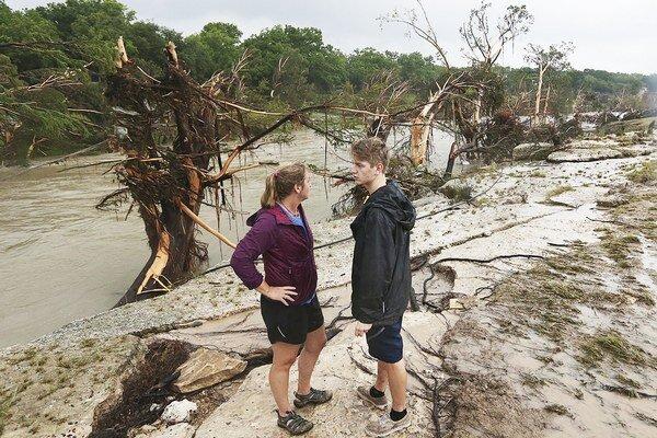 Shelly Guzalová a jej syn stoja na mieste, kde rieka strhla chatku s dvoma rodinami.