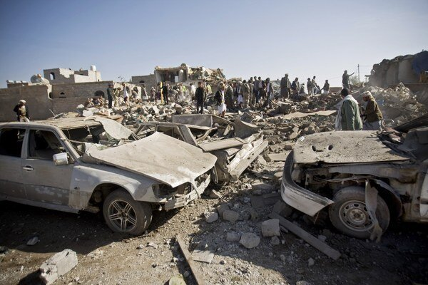 Ľudia prehľadávajú trosky domov a pátrajú po ľuďoch, ktorí prežili letecký útok na obytnú štvrť pri letisku v jemenskom meste Saná 26. marca 2015.