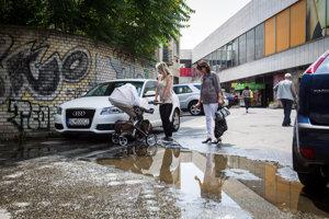 Aj deň po daždi sa ľudia brodia mlákou.