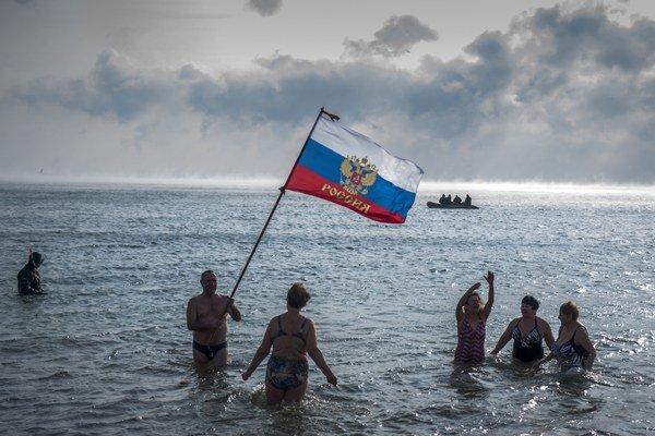 Obyvatelia Krymu sa kúpu v Čiernom mori s ruskou vlajkou.