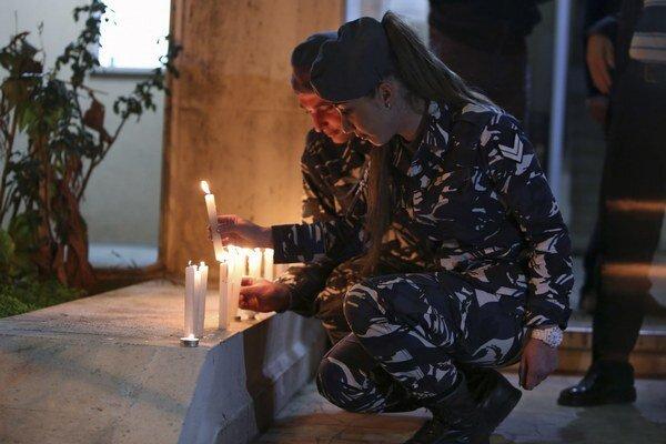 Libanonská policajtka zapaľuje sviečku na počesť upáleného jordánskeho pilota.