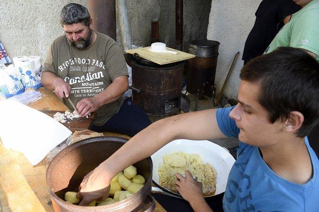 Otec so synom pripravujú bryndzové halušky v jednom z domov.