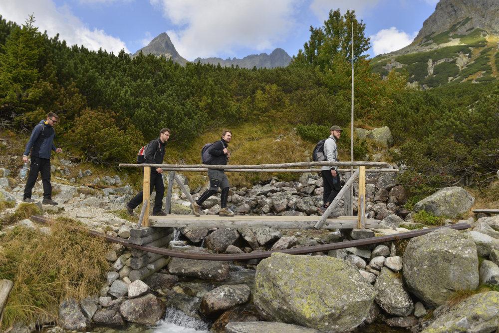 Turisti prechádzajú lávkou ponad Žabí potok, vľavo v pozadí je Mengusovský Volovec.