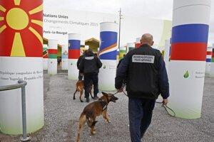 Na snímke francúzski policajti so psami, ktorí su vycvičení na hľadanie bômb, hliadkujú pred vchodom dejiska klimatického samitu OSN v Paríži 30. novembra 2015.