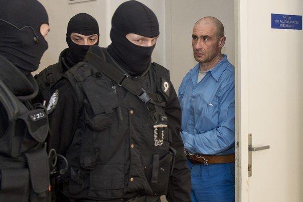 Obžalovaný Ľuboš F. v sprievode polície odchádza z prerušeného  súdneho pojednávania 10. marca 2015 v Bratislave.