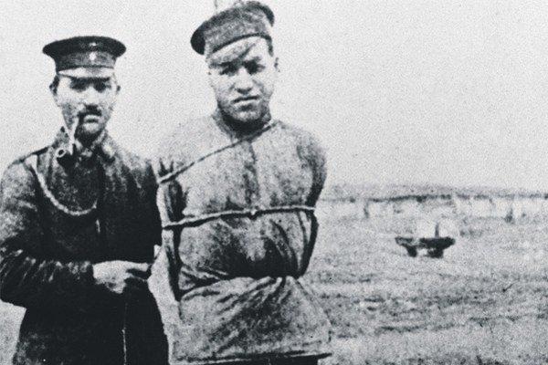 Ruský zajatec nemeckej armády priviazaný o kôl.