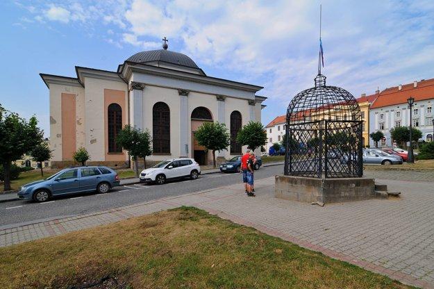 Klietka hanby vedľa radnice  na Námestí Majstra Pavla, v pozadí evanjelický kostol z 19. storočia.