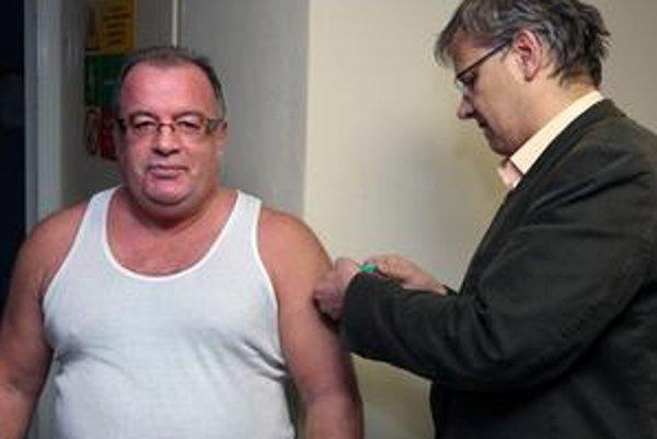 Lekár Peter Lipták dáva vakcínu hlavnému hygienikovi Ivanovi Rovnému.