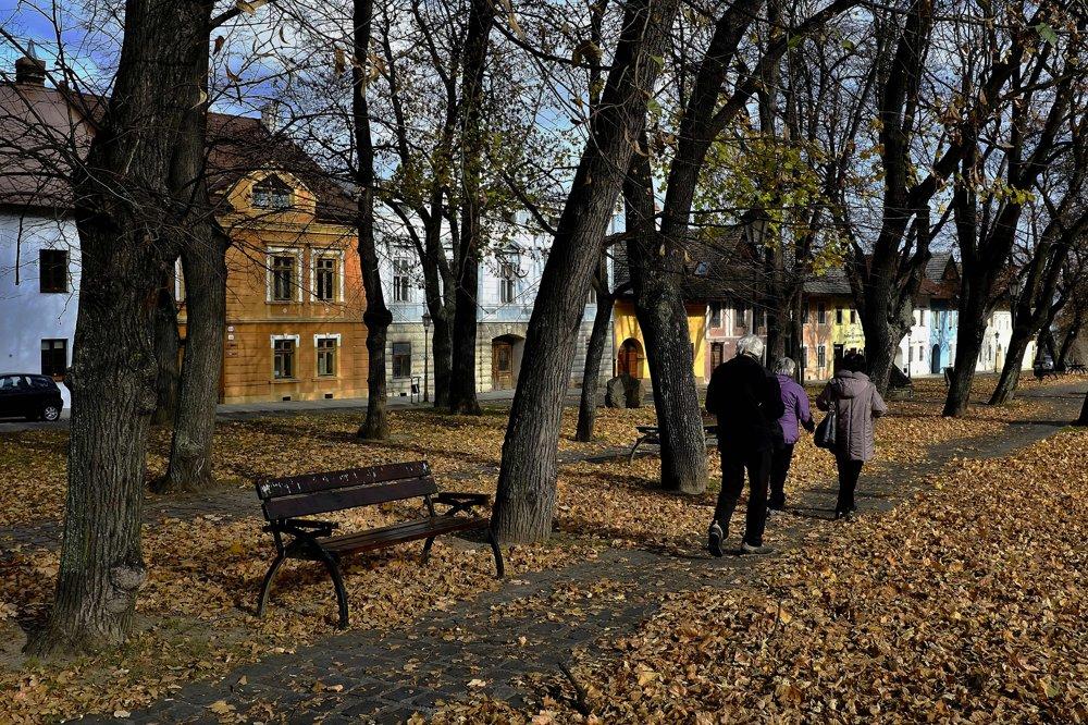 Na snímke ľudia prechádzajú parkom v časti historického námestia s renesančnými domami.