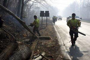 Muži odstraňujú zhorené a popadané stromy po požiaroch v Tennessee.