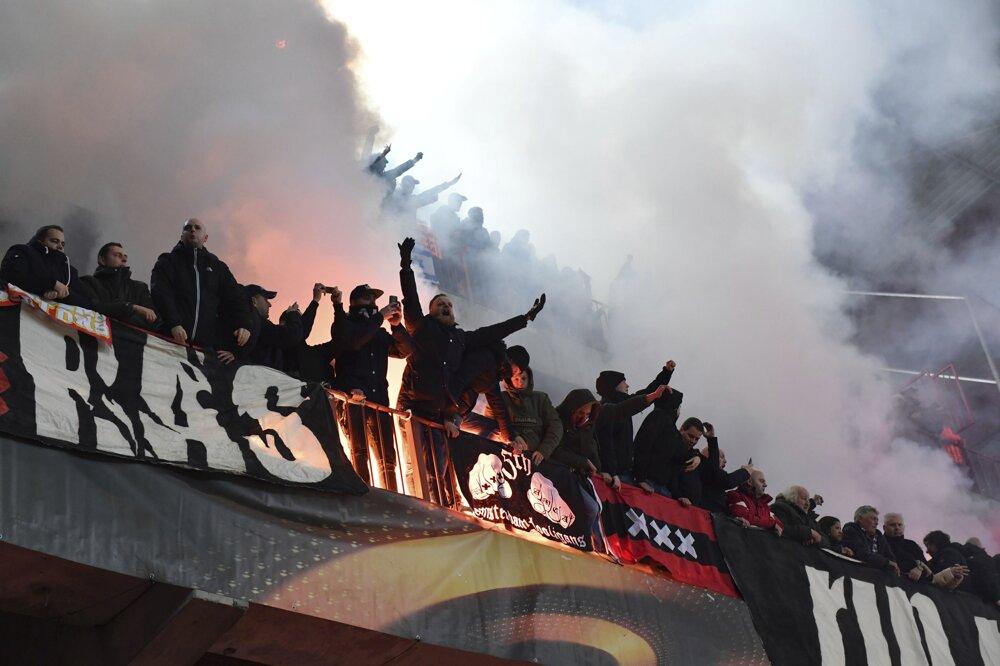 Fanúšikovia zapaľujú svetlice v hľadisku v zápase G-skupiny 6. kola Európskej ligy vo futbale Standard Liege - Ajax Amsterdam.  FOTO - TASR/AP