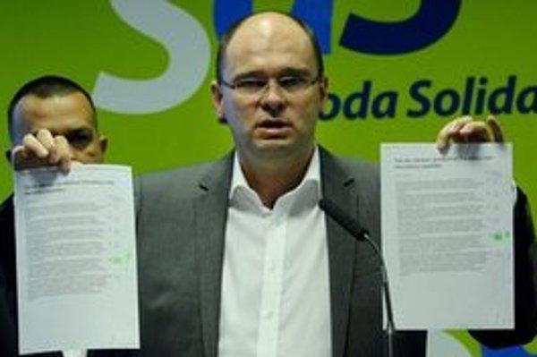 Richard Sulík ukazuje návrhy zákona na tlačovej konferencii.