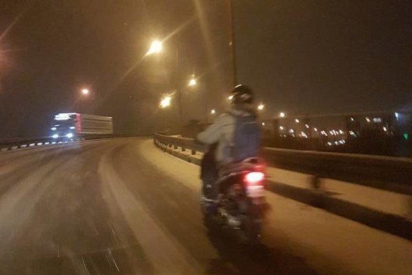 Odvážny motocyklista na zasneženej ceste.