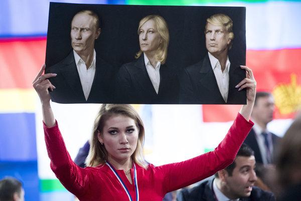 Ruská novinárka drží plagát s vyobrazeniami Putina, Le Penovej a Trumpa pred prezidentovou výročnou tlačovou konferenciou 23.decembra 2016.