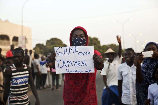 """Muž v meste Serrekunda drží v rukách nápis """"Je koniec, Jammeh."""" po tom, čo novozvolený prezident Gambie Adama Barrow zložil sľub."""