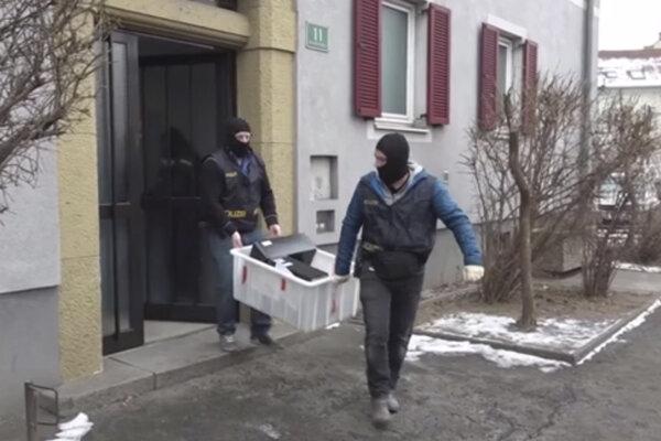 Na videosnímke rakúski policajti odnášajú počítače z domu počas policajnej operácie v rakúskom meste Graz.
