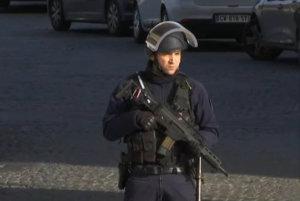Policajt so samopalom hliadkuje pri budove múzea.