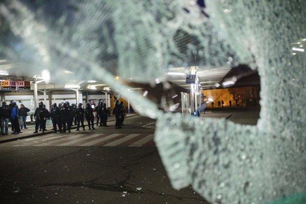 Pohľad na políciu a protestujúcich cez rozbité okno počas nočných násilností.