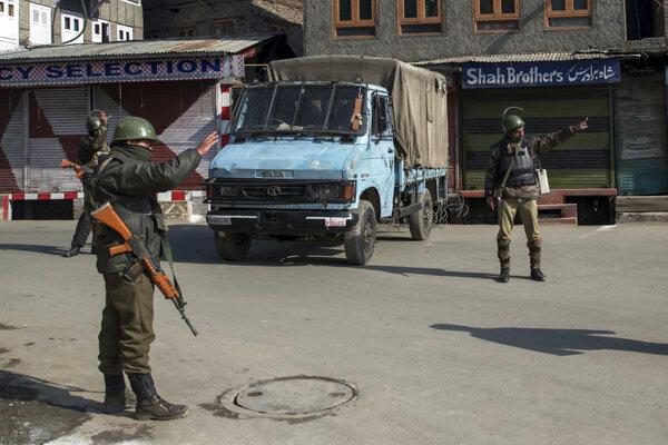 Na snímke indickí polovojenskí vojaci zastavujú civilistov počas zákazu vychádzania v meste Šrínagar 9. februára 2017. Zákaz bol vydaný z obavy pred nepokojmi vzhľadom na výročie popravy kašmírskeho krajana Afzala Guru (9. februára 2013) za útok na indický parlament z roku 2001.